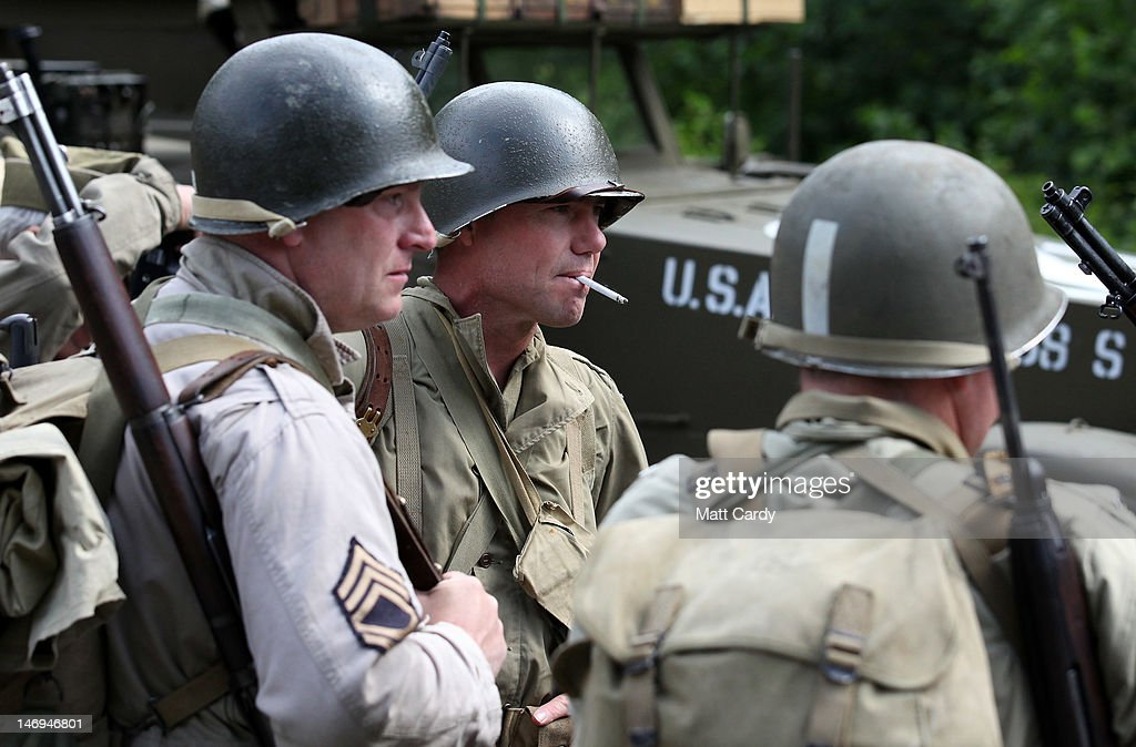Re-enactors dressed as American soldiers wait to get onto a truck as a convoy of Second World War vehicles prepare to leave the village as part of the two-day Maiden Newton At War 1940s re-enactment weekend in Maiden Newton on June 23, 2012 near Dorchester, England. The quiet Dorset village of Newton Maiden was seen as a strategic hub during the Second World War and was heavily fortified against a threatened German invasion. It later saw hundreds of American servicemen quartered in the area before the D Day landings. To celebrate the village's wartime past, the biennial event, which started in 2008, has grown into one of the biggest re-enactments in the country and this year featured one of the largest convoys of Second World War vehicles seen in Dorset since D Day in 1944.