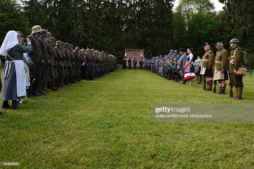 Reenactors dressed as French and German soldiers take part in a ceremony at the German WWI cemetery of Troyon, eastern France, on May 28, 2016, as part of the 100-year commemoration of WWI's Battle of Verdun. VERHAEGEN