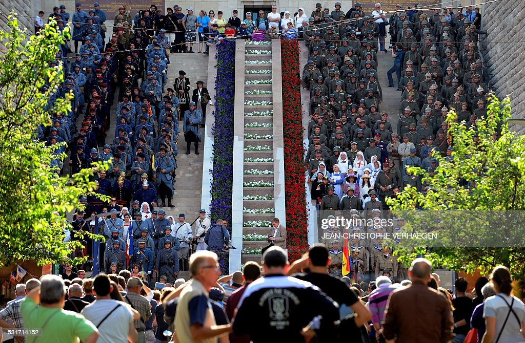 Reenactors dressed as French soldiers (L) and German soldiers are pictured in front of at the Victory Monument before the remembrance of the centenary of the battle of Verdun, on May 27, 2016 in Verdun, eastern France. / AFP / JEAN
