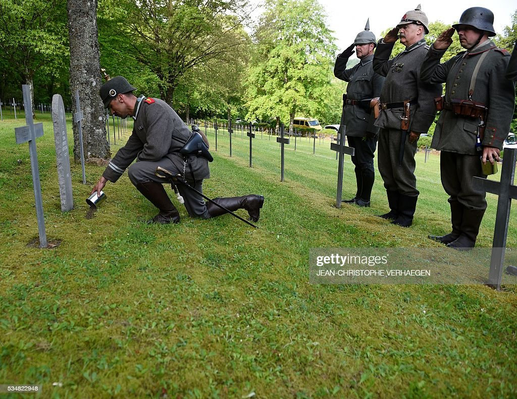 Reenactors dressed as German soldiers pay their respects and leave German soil at the foot of tombstones and crosses at the German WWI cemetery of Troyon, eastern France, on May 28, 2016, as part of the 100-year commemoration of WWI's Battle of Verdun. VERHAEGEN