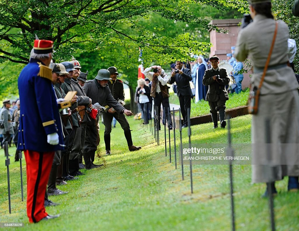 Reenactors pay their respects and leave German soil on the graves of soldiers at the German WWI cemetery of Troyon, eastern France, on May 28, 2016, as part of the 100-year commemoration of WWI's Battle of Verdun. VERHAEGEN