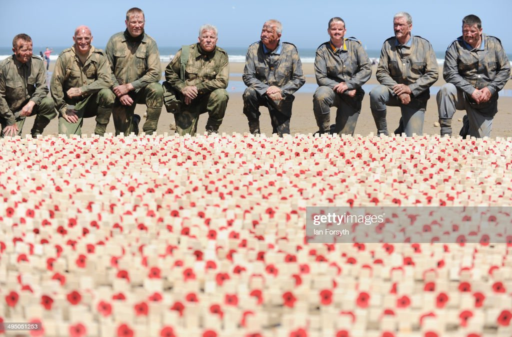 Re-enactors pose next to poppy crosses planted in the sand during a commemoration event to remember the World War one truce football match on June 1, 2014 in Saltburn-by-the-Sea, England. The Christmas truce football match was one of many unofficial ceasefires that took place along the western front around Christmas 1914 during World War one.