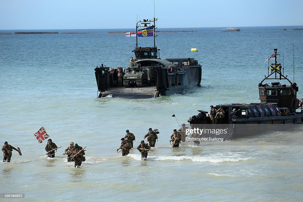 Re-enactors storm Gold Beach from a Royal Marine Landing craft during the 70th anniversary of the D-Day landings parade on June 6, 2014 in Arromanches Les Bains, France. Friday 6th June is the 70th anniversary of the D-Day landings which saw 156,000 troops from the allied countries including the United Kingdom and the United States join forces to launch an audacious attack on the beaches of Normandy, these assaults are credited with the eventual defeat of Nazi Germany. A series of events commemorating the 70th anniversary are planned for the week with many heads of state travelling to the famous beaches to pay their respects to those who lost their lives.