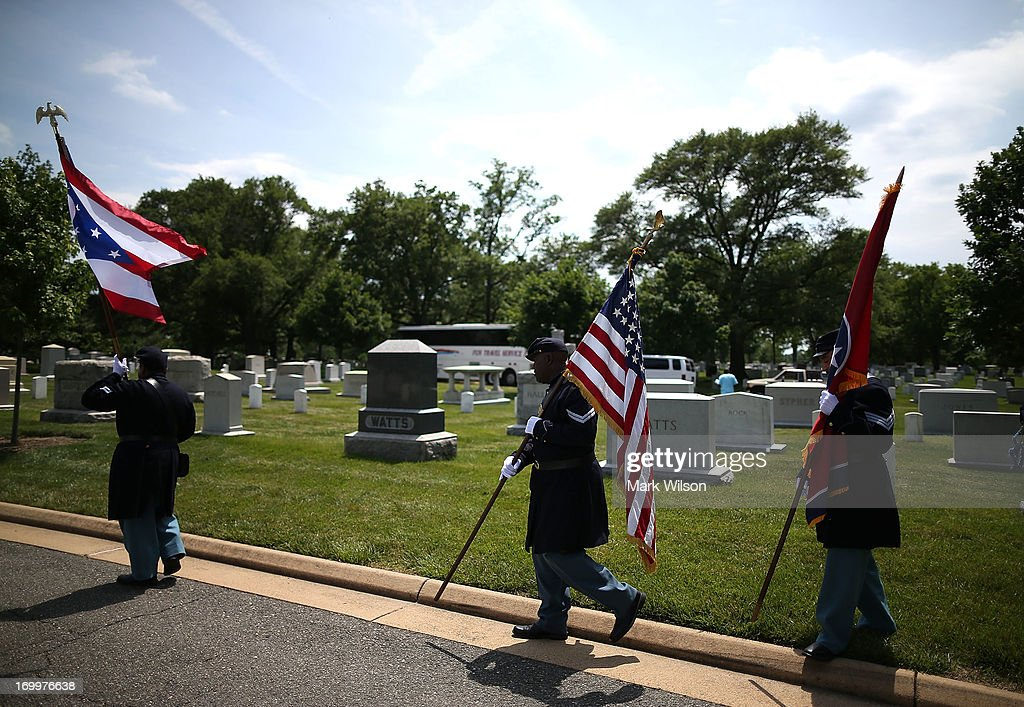 Reenactos dressed in period clothing carry flags an event at the gravesite of Buffalo Soldier Col. Charles Young, at Arlington Cemetery, June 5, 2013 in Arlington, Virginia. The event was hosted by the National Coalition of Black Veterans and the Omega Psi Phi Fraternity to celebrate the 90th anniversary of 'Buffalo Soldier' and military leader Col. Charles Young's internment in Arlington Cemetery.