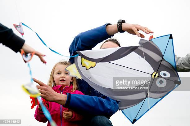 Reese Bethel of Falmouth looks concerned about the fate of her kite as her father George at right tries to untangle its line with a few other kites...