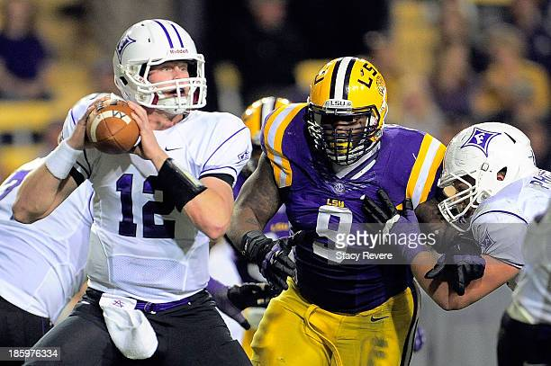 Reese Hannon of the Furman Paladins is pressured by Ego Ferguson of the LSU Tigers during a game at Tiger Stadium on October 26 2013 in Baton Rouge...
