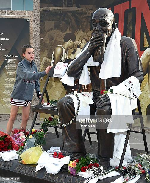 Reese Rivera of Nevada places a towel at a statue of Jerry Tarkanian outside the Thomas Mack Center at UNLV during a gathering of fans for the...