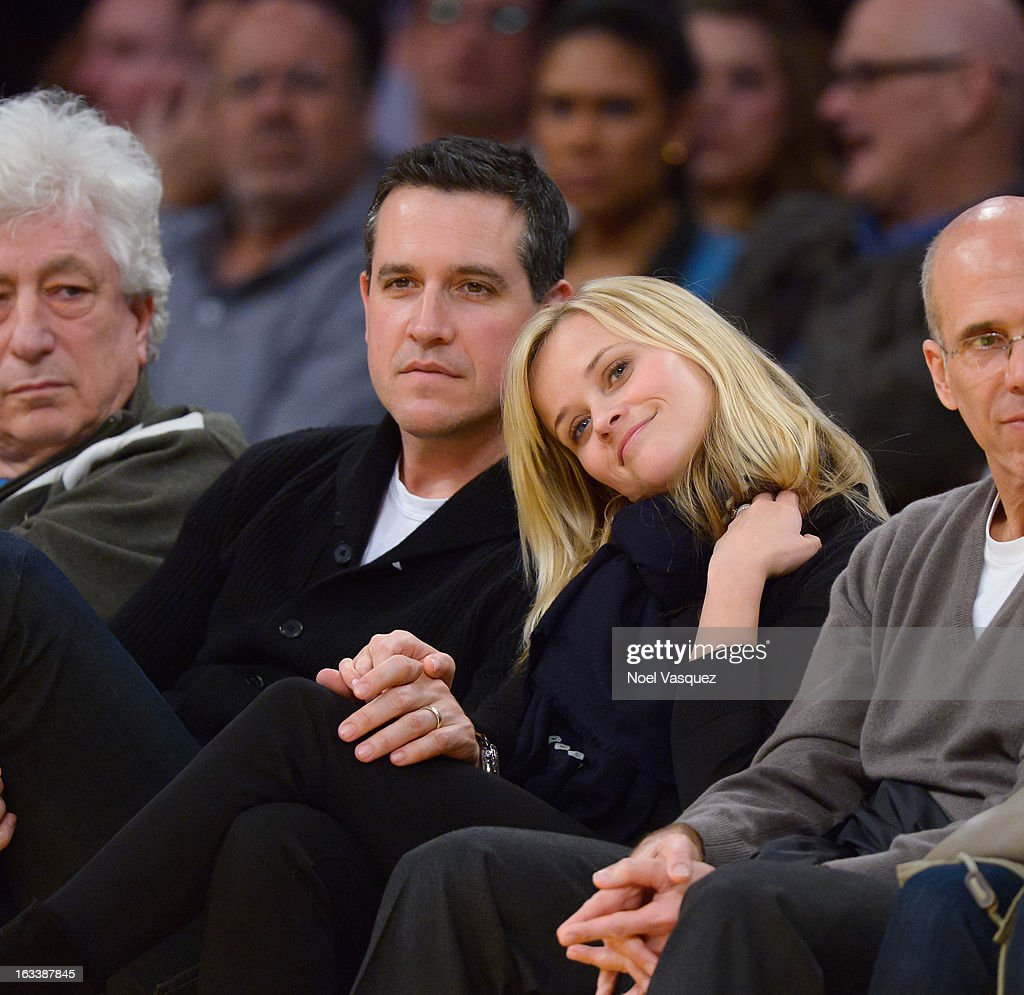 Reese Witherspoon and her husband Jim Toth attend a basketball between Toronto Raptors and Los Angeles Lakers at Staples Center on March 8 2013 in...