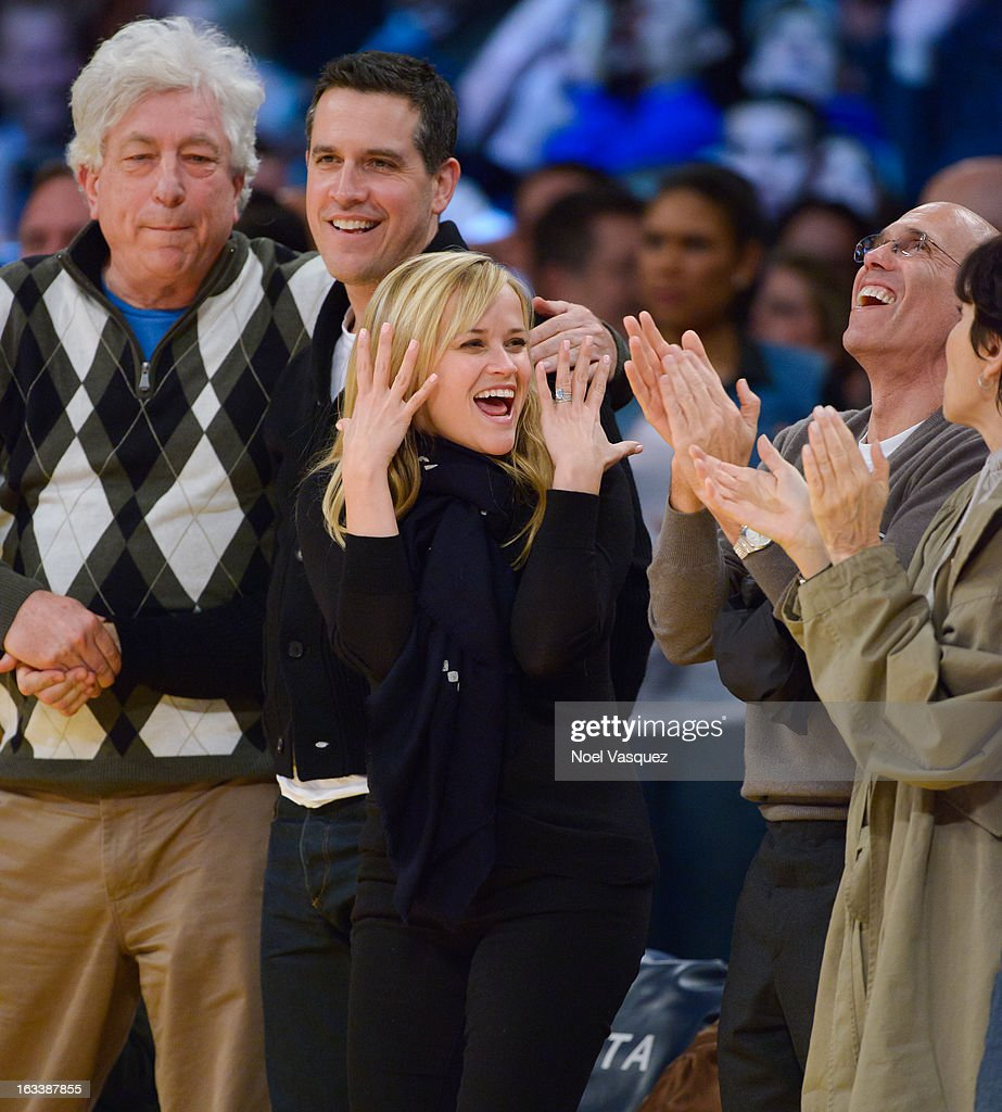 Reese Witherspoon (R) and her husband Jim Toth attend a basketball between Toronto Raptors and Los Angeles Lakers at Staples Center on March 8, 2013 in Los Angeles, California.