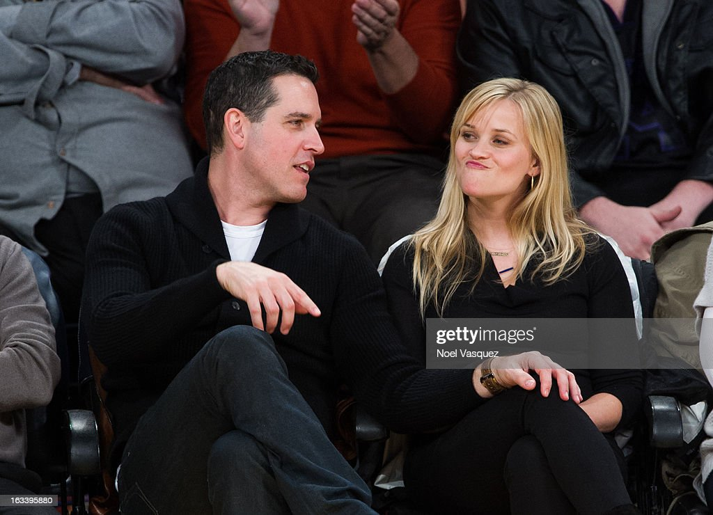 Reese Witherspoon (R) and her husband Jim Toth attend a basketball game between the Toronto Raptors and Los Angeles Lakers at Staples Center on March 8, 2013 in Los Angeles, California.