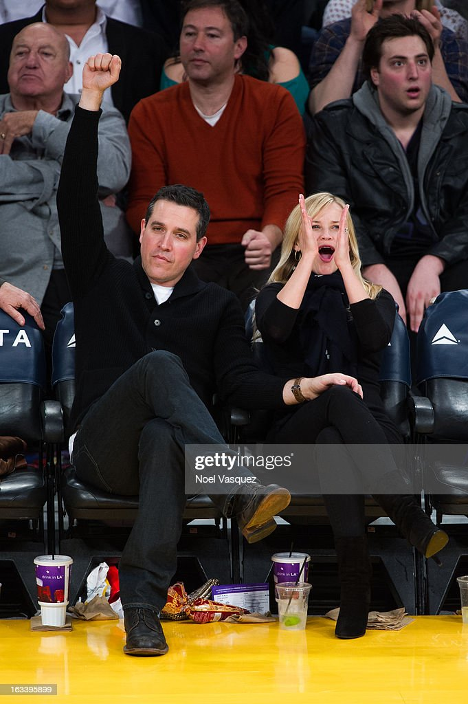Reese Witherspoon (R) and her husband Jim Toth attends a basketball game between the Toronto Raptors and Los Angeles Lakers at Staples Center on March 8, 2013 in Los Angeles, California.