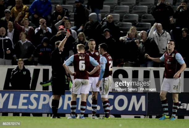 Refeeree Robert Madley shows Burnley's Keith Tracy a red card during the Capital One Cup Fourth Round match at Turf Moor Burnley