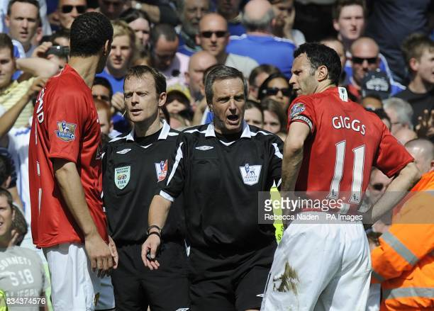 Referee Alan Wiley holds back Manchester United's Rio Ferdinand and Ryan Giggs after the linesman penalised Manchester United's Michael Carrick for...