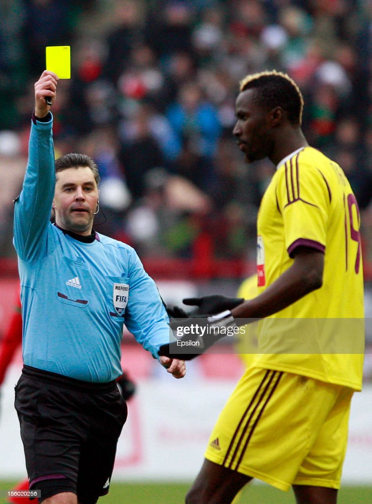 Referee Aleksei Nikolayev shows <a gi-track='captionPersonalityLinkClicked' href=/galleries/search?phrase=Lacina+Traore&family=editorial&specificpeople=6515667 ng-click='$event.stopPropagation()'>Lacina Traore</a> of the FC Anzhi Makhachkala a yellow card during the Russian Premier League match between FC Lokomotiv Moscow and FC Anzhi Makhachkala at the Lokomotiv Stadium on November 11, 2012 in Moscow, Russia.
