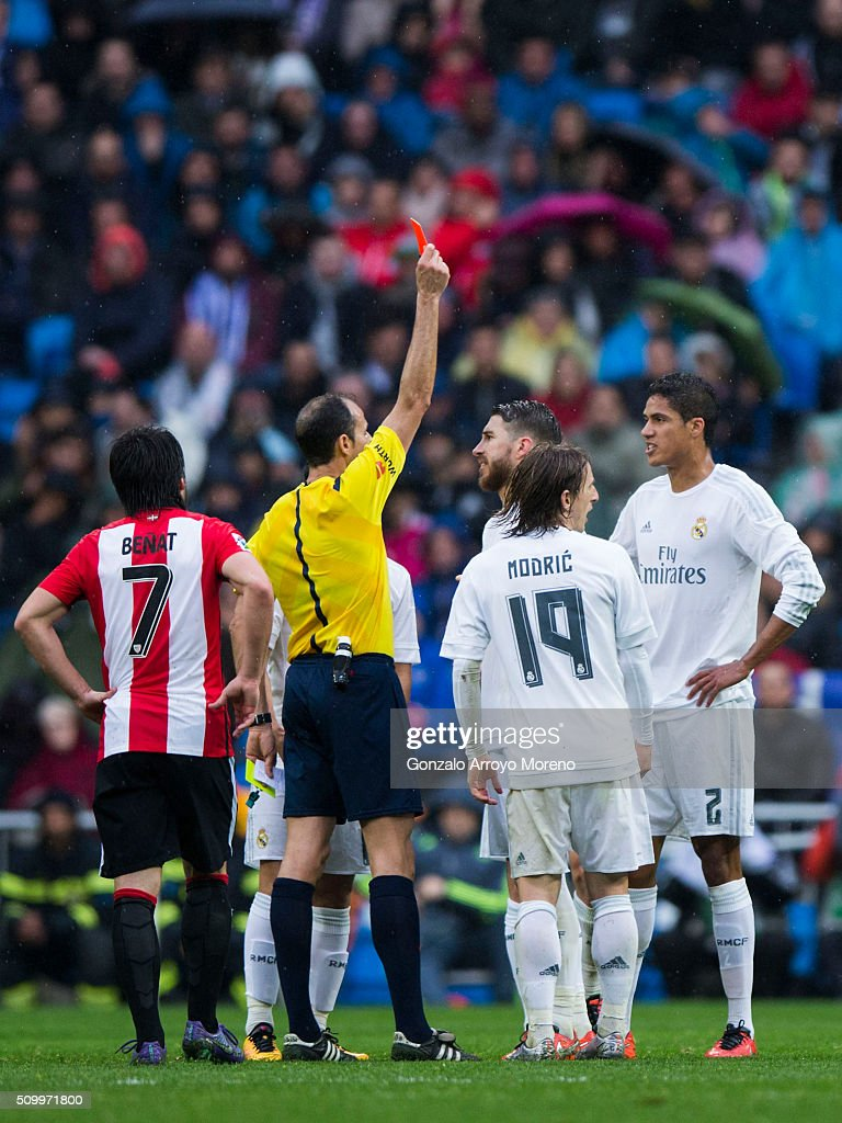 Referee Alfonso Javier Alvarez Izquierdo (2ndL) shows the red card to Raphael Varane (R) during the La Liga match between Real Madrid CF and Athletic Club at Estadio Santiago Bernabeu on February 13, 2016 in Madrid, Spain.