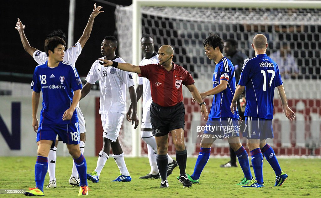UAE referee Ali Hamad gestures towards players during the match between South Korea's Suwon Samsung Bluewings club against Qatar's Al-Sadd club in their semi-final football match in the AFC Champions League in Doha, on October 26, 2011. Suwon Samsung Bluewings won the match 1-0. AFP PHOTO/KARIM JAAFAR