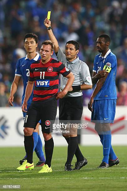 Referee Alireza Faghani gives Brendan Santalab of the Wanderers a yellow card during the Asian Champions League final match between the Western...