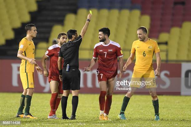 Referee Alireza Faghani of the Islamic Republic of Iran shows Omar Khrbin of Syra the yellow card during the FIFA 2018 World Cup Asian Playoff Leg 1...