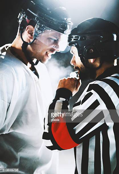 Referee and ice hockey player in an argument.