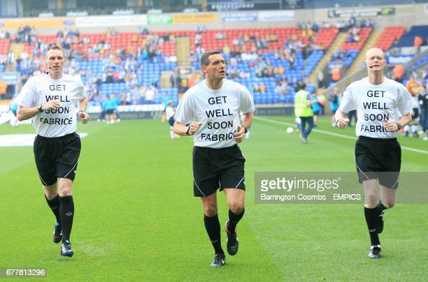 Referee Andre Marriner and the assistant referee's wear Get Well Soon Fabrice shirts as they warm up prior to kick off
