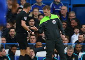 Referee Andre Marriner hands coins to fourth official Mike Jones after they were allegedly thrown as David Faupala of Manchester City celebrated his...