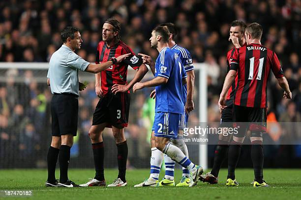 Referee Andre Marriner is surrounded by players after he awards a late penalty to Chelsea during the Barclays Premier League match between Chelsea...