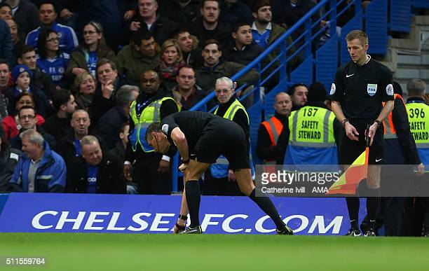 Referee Andre Marriner picks up items thrown onto the pitch after David Faupala of Manchester City scores to make it 11 during the Emirates FA Cup...