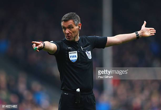 Referee Andre Marriner points during the Barclays Premier League match between Crystal Palace and Liverpool at Selhurst Park on March 6 2016 in...