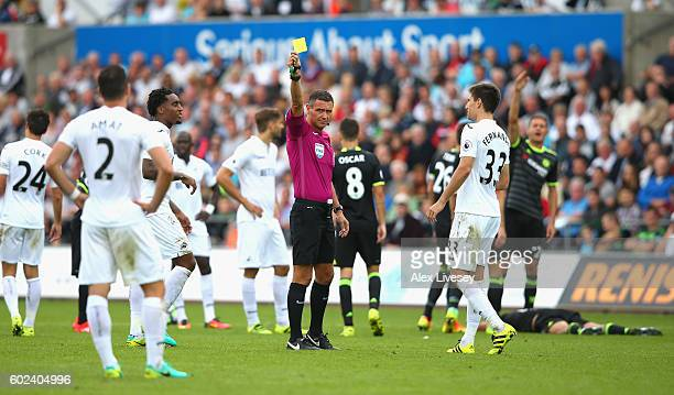 Referee Andre Marriner shows a yellow card to Jordi Amat of Swansea City during the Premier League match between Swansea City and Chelsea at Liberty...