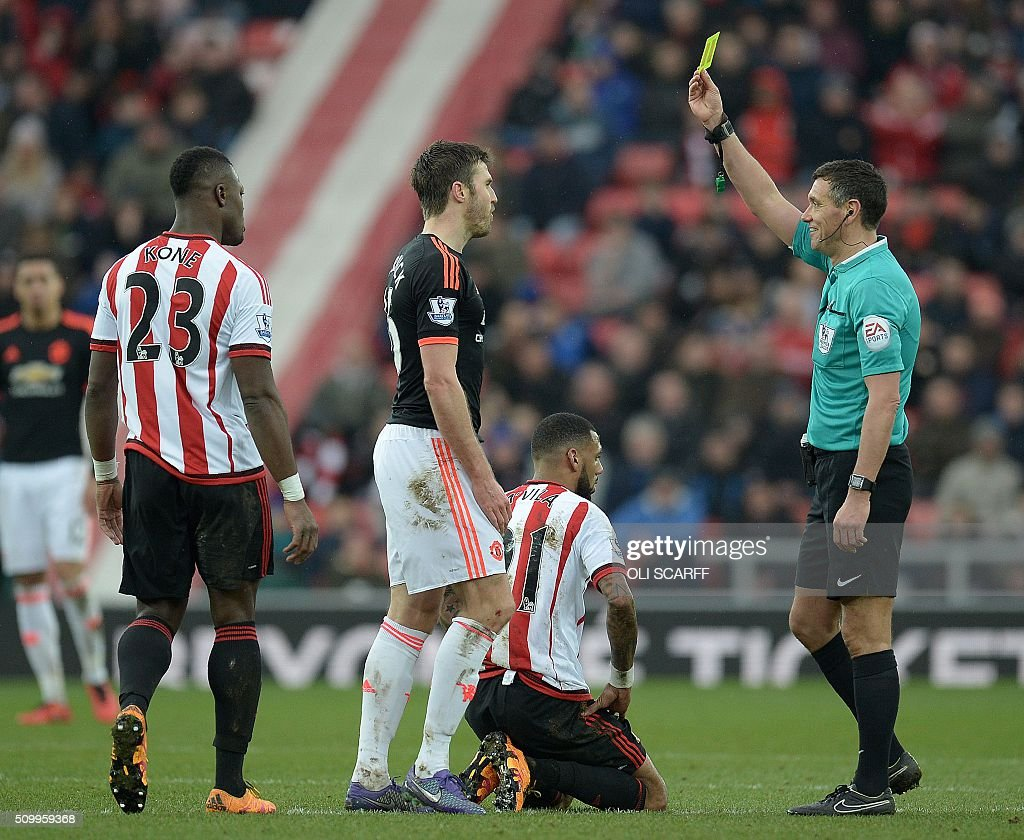 Referee Andre Marriner (R) shows a yellow card to Manchester United's English midfielder Michael Carrick (C) following a challenge on Sunderland's French midfielder Yann M'vila (2R) during the English Premier League football match between Sunderland and Manchester United at the Stadium of Light in Sunderland, northeast England on February 13, 2016. / AFP / OLI SCARFF / RESTRICTED TO EDITORIAL USE. No use with unauthorized audio, video, data, fixture lists, club/league logos or 'live' services. Online in-match use limited to 75 images, no video emulation. No use in betting, games or single club/league/player publications. /