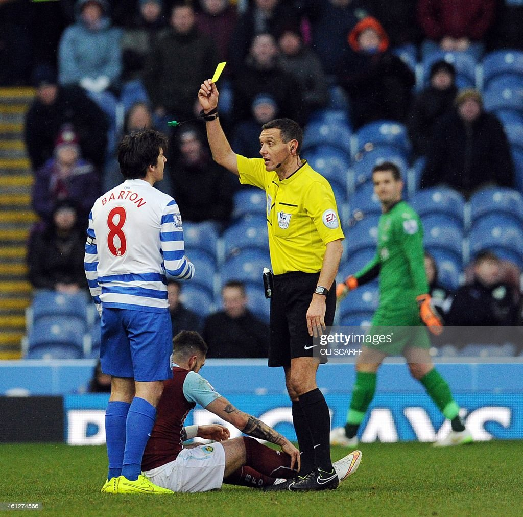Referee Andre Marriner shows a yellow card to Queens Park Rangers' English midfielder Joey Barton during the English Premier League football match...