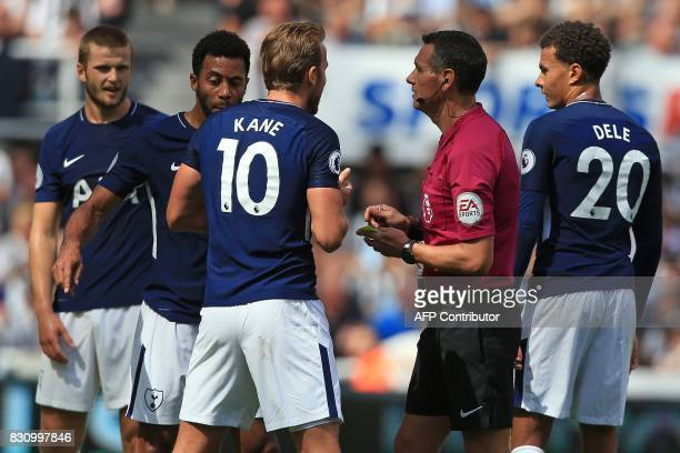 Referee Andre Marriner shows a yellow card to Tottenham Hotspur's English striker Harry Kane during the English Premier League football match between...