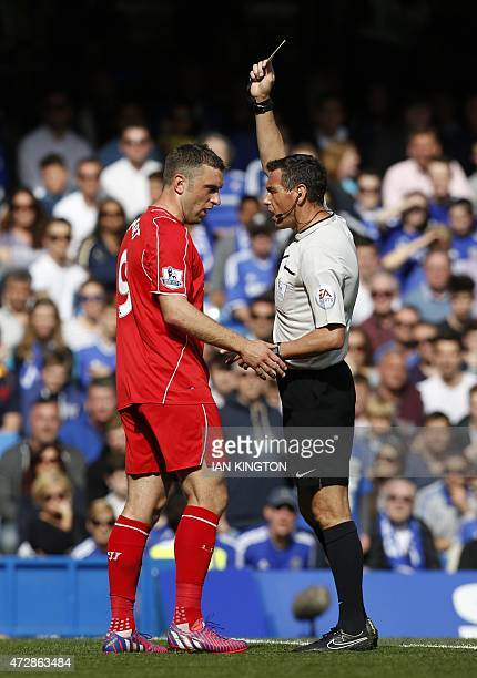 Referee Andre Marriner shows Liverpool's English striker Rickie Lambert a yellow warning card during the English Premier League football match...