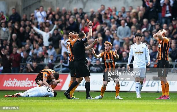 Referee Andre Marriner shows the red card to David Meyler of Hull City during the Barclays Premier League match between Swansea City and Hull City at...