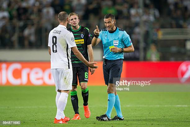 Referee Andre Marriner shows yellow card to Jan Lecjaks of YB Bern next to Christoph Kramer of Moenchengladbach during the UEFA Champions League...