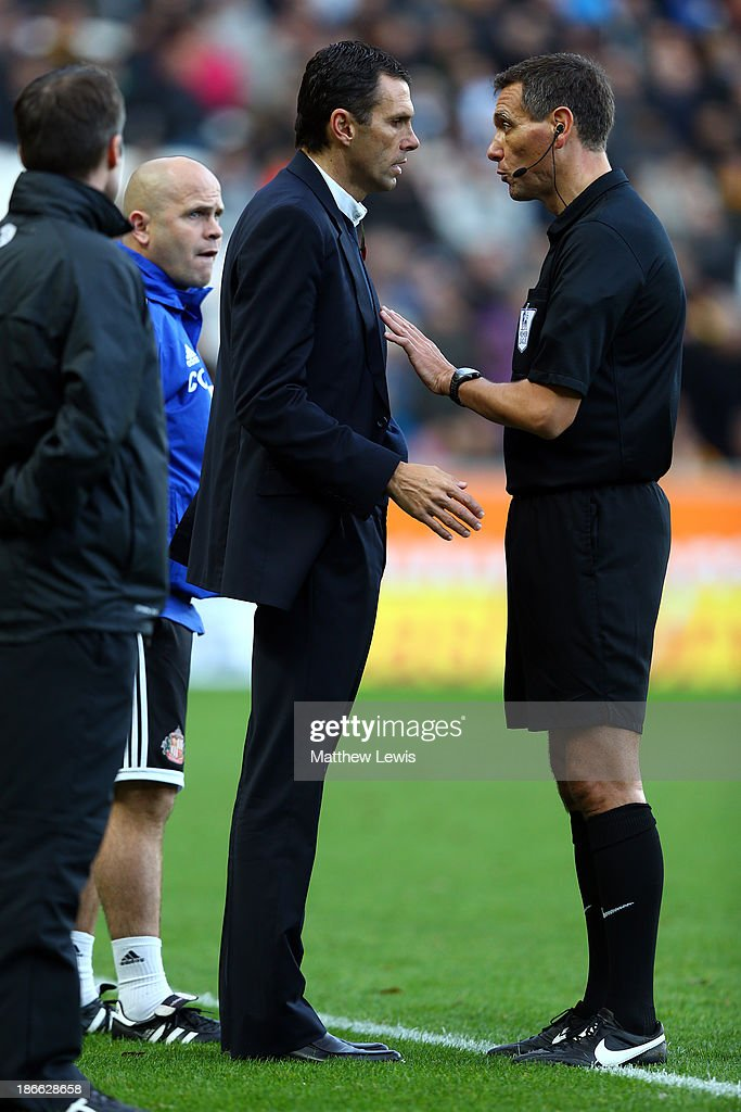 Referee Andre Marriner (C) speaks with Sunderland manager Gus Poyet during the Barclays Premier League match between Hull City and Sunderland at KC Stadium on November 2, 2013 in Hull, England.