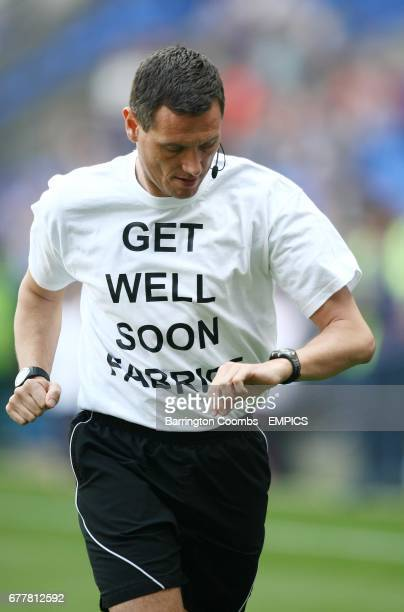 Referee Andre Marriner wears a Get Well Soon Fabrice shirt as he warms up