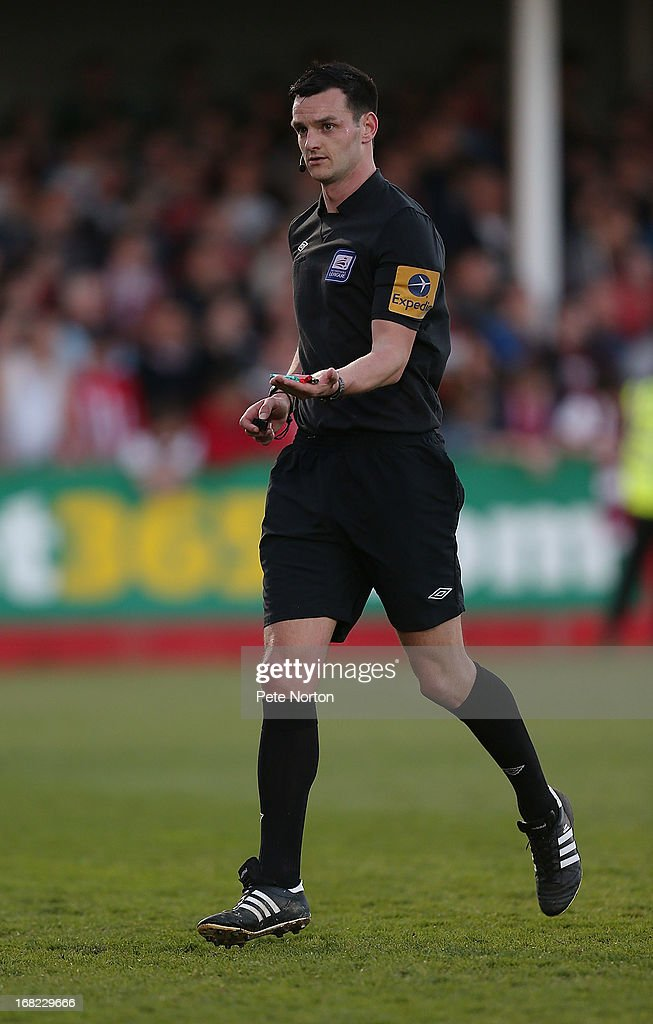 Referee Andrew Madley removes items thrown onto the pitch during the npower League Two Play Off Semi Final Second Leg between Cheltenham Town and Northampton Town at Abbey Business Stadium on May 5, 2013 in Cheltenham, England.