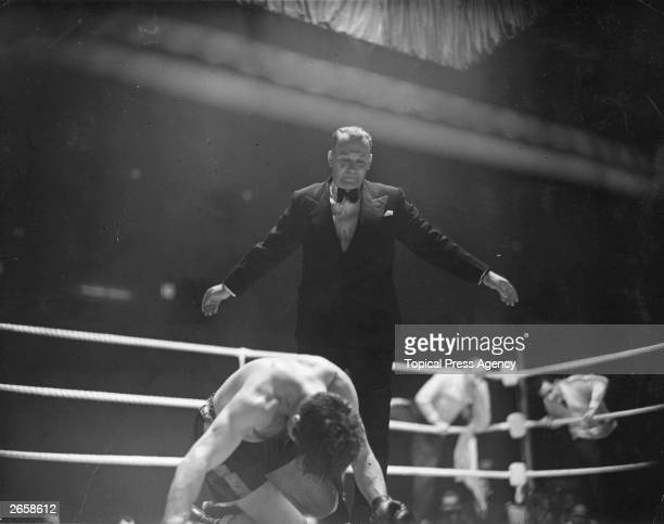 Referee Andrew Smythe signals the end of the count on Freddie Mills at the end of his world title lightheavyweight fight against Joey Maxim in London