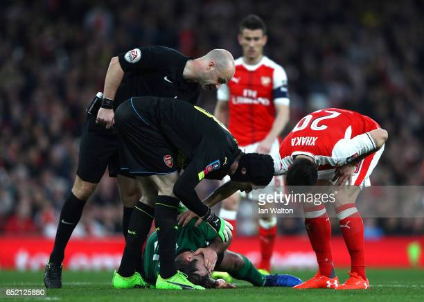 Referee Anthony Taylor and Petr Cech and Shkodran Mustafi of Arsenal stand over an injured Matt Rhead of Lincoln City during The Emirates FA Cup...