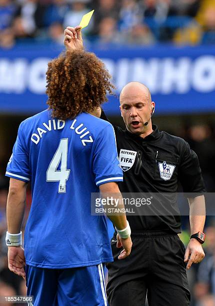 Referee Anthony Taylor gives Chelsea's Brazilian defender David Luiz a yellow card following a tackle on Cardiff City's Icelandic midfielder Aron...