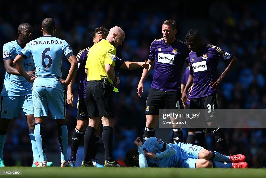 Referee Anthony Taylor looks on as David Silva of Manchester City lies injured after a foul from Cheikhou Kouyate of West Ham during the Barclays Premier League match between Manchester City and West Ham United at Etihad Stadium on April 19, 2015 in Manchester, England.