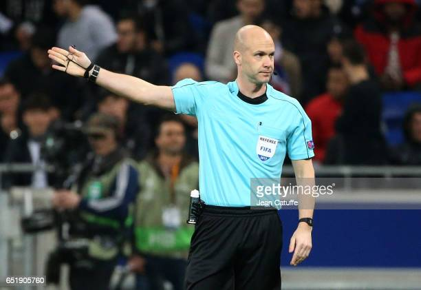 Referee Anthony Taylor of England gestures during the UEFA Europa League Round of 16 first leg match between Olympique Lyonnais and AS Roma at Parc...