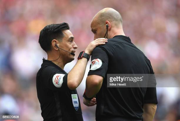 Referee Anthony Taylor seaks to Garry Beswick assistant referee during The Emirates FA Cup Final between Arsenal and Chelsea at Wembley Stadium on...