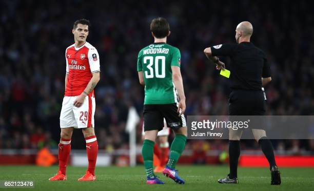 Referee Anthony Taylor shows a yellow card to Granit Xhaka of Arsenal during The Emirates FA Cup QuarterFinal match between Arsenal and Lincoln City...