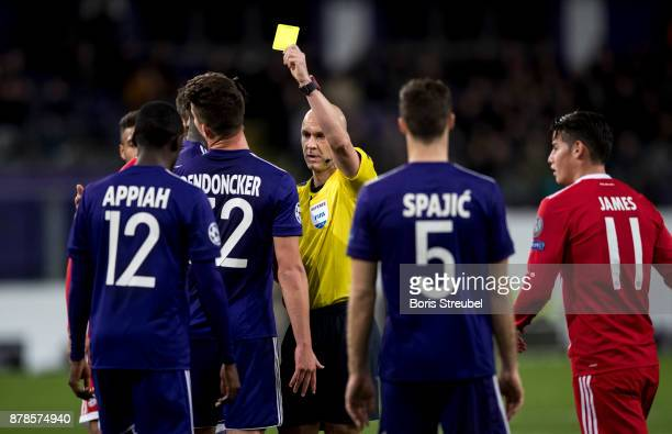 Referee Anthony Taylor shows a yellow card to Leander Dendoncker of Anderlecht during the UEFA Champions League group B match between RSC Anderlecht...