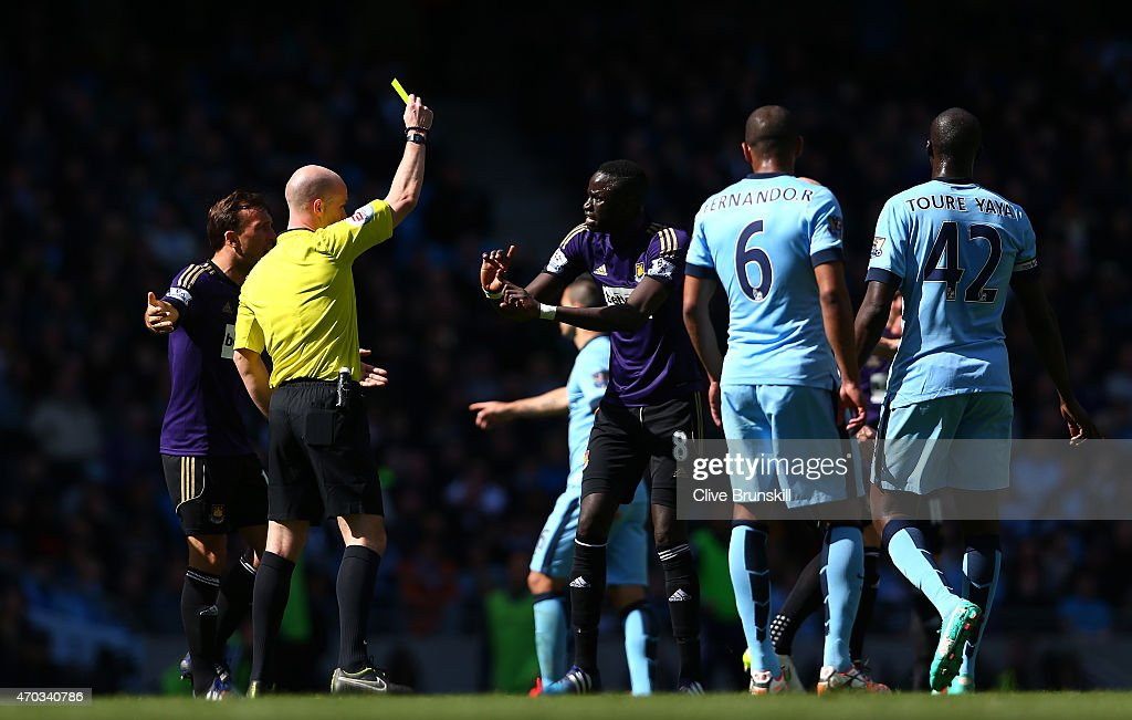 Referee Anthony Taylor shows Cheikhou Kouyate of West Ham a yellow card for a foul on David Silva of Manchester City during the Barclays Premier League match between Manchester City and West Ham United at Etihad Stadium on April 19, 2015 in Manchester, England.