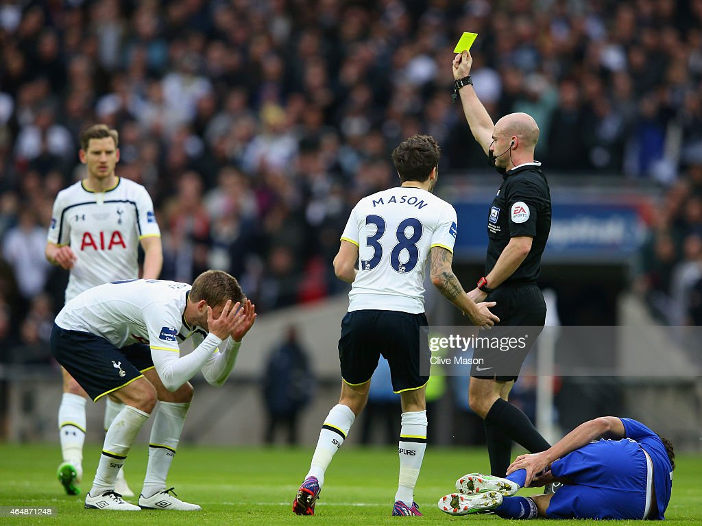 Referee Anthony Taylor shows Eric Dier of Spurs a yellow card for a challenge on Diego Costa of Chelsea during the Capital One Cup Final match...