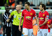 Referee Anthony Taylor steps in as Manchester United player Jonny Evans and Papiss Cisse of Newcastle have words during the Barclays Premier League...