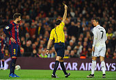 Referee Antonio Miguel Mateu Lahoz shows a yellow card to Cristiano Ronaldo of Real Madrid CF during the La Liga match between FC Barcelona and Real...